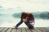 Depressed and stressed woman sitting on wooden pier - 184051717