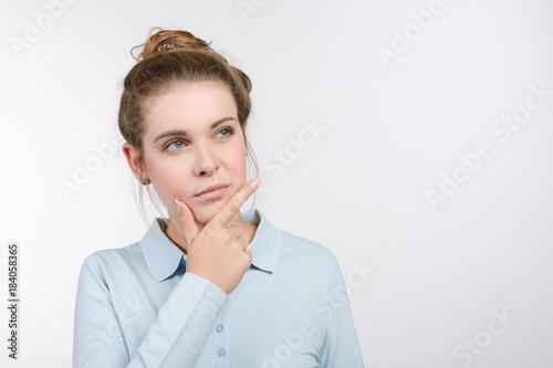 canvas print picture junge Frau denkt über etwas nach und reibt sich das Kinn