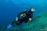 woman scuba diving over rocks in the Mediterranean Sea - 184063759