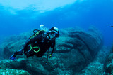 woman scuba diving over rocks in the Mediterranean Sea - 184068180