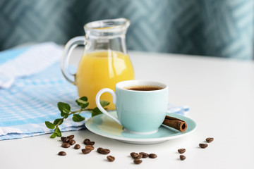 Strong black coffee in a light blue cup on a white table with orange juice