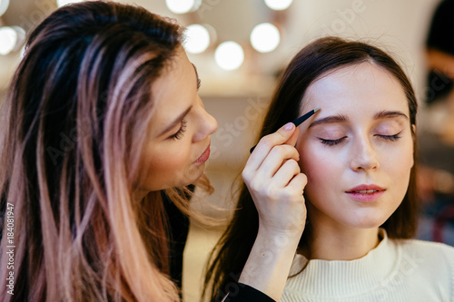Leinwanddruck Bild Eyebrow correction. Beautician correction eye brow procedure for the model with long eyelashes in beauty salon. Beauty concept.