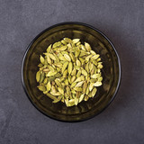 Cardamom seeds in a bowl on a grey concrete background - 184087901
