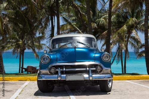 Amerykański niebieski Chevrolet klasyczny samochód zaparkowany na plaży pod palmami w Varadero na Kubie - reportaż z serii Kuba
