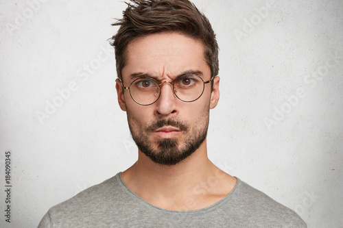 Plexiglas Kapsalon Headshot of strict annoyed aggressive man with beard, mustache, looks seriously through round spectacles, frowns face in dissatisfaction, expresses negative emotions, isolated over white concrete wall
