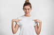 Horizontal shot of glad delightful female dressed in casual t shirt, indicates with fore fingers at blank space, being satisfied with new purchase. Advertising, clothing, people and design concept