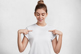 Horizontal shot of glad delightful female dressed in casual t shirt, indicates with fore fingers at blank space, being satisfied with new purchase. Advertising, clothing, people and design concept - 184090548