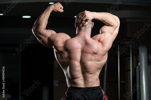 Biceps Pose Of A Young Man In Gym