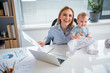 Top view cheerful mother having job at desk and taking care of baby in room. Profession and infant concept