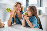 Cheerful girl is biting a green apple with appetite. Her mother is looking at her with love and smiling. Healthy lifestyle concept