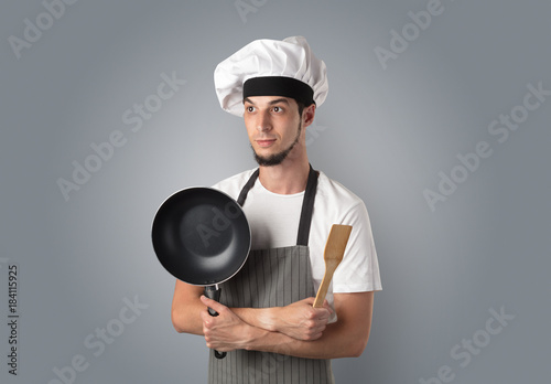 Cook with kitchen tools and empty wallpaper