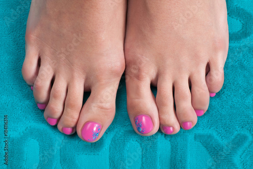Tuinposter Pedicure Close-up shot of beautiful woman feet with pedicure on blue towel