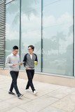 Two smiling young businessmen walking and talking in the city - 184126722