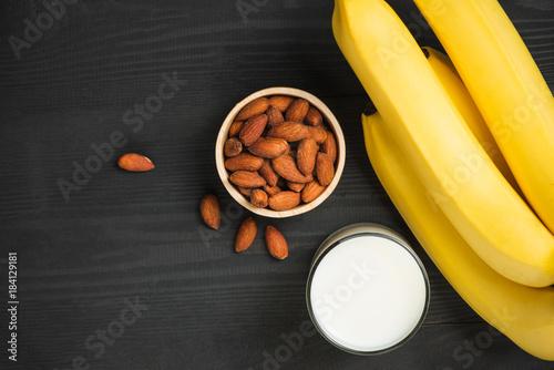 Foto op Plexiglas Milkshake A banch of bananas with almonds and milk on wooden background.