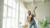 Funny bearded man dance on bed singing and playing electric guitar in bedroom at home - 184131791