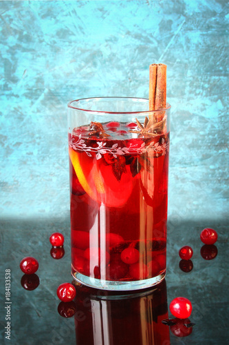Spicy Christmas drink in a glass with spices, cranberries and lemon