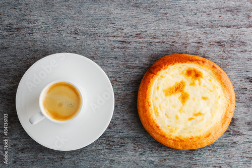 Wall mural a cup of espresso on a plate and a bun on a wooden background