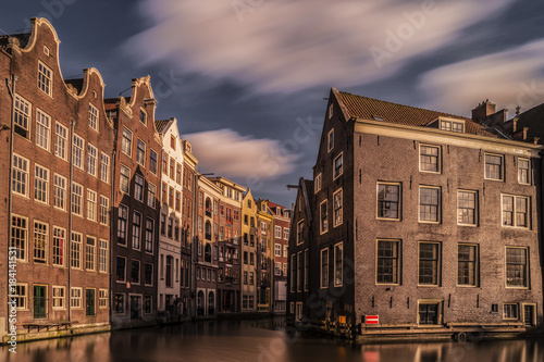 Foto op Plexiglas Amsterdam Amsterdam city at night with colorful house and passenger boats alongside the canal, Amsterdam Netherlands