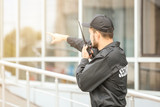 Fototapety Male security guard using portable radio transmitter near building outdoors