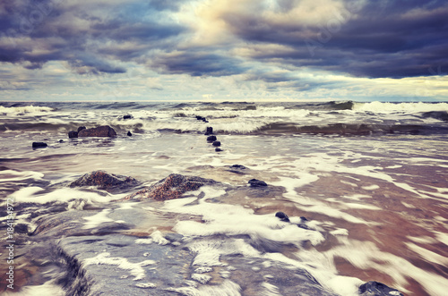 Vintage toned picture of a beach with stormy sky, motion blurred water..