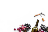 Open the wine. Corkscrew near bottle and grape on white background top view copyspace