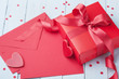 Envelope, gift, paper card and red heart on blue table for greeting on Valentines Day.