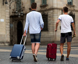Rear view of two guys with luggage - 184176171