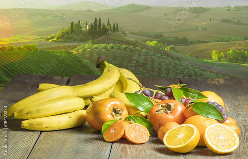 Keuken foto achterwand Oranje fruits on a wooden table, in the background the landscape of Italian Tuscany