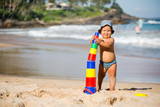 Kid plays with toys at the seashore in summertime - 184181519