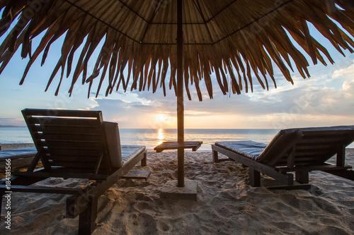 Foto Murales Sun loungers with umbrella on the beach, sunrise