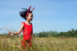 Asian Wearing Reindeer Headband and Running in the Meadow.