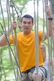handsome man crossing a rope bridge