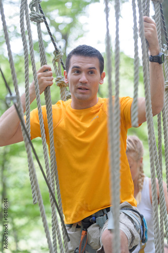 Wall mural handsome man crossing a rope bridge