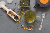 cup of green tea and dried tea on grey stone table - 184186919
