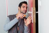 happy young carpenter fixing broken door lock - 184188392