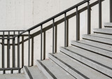 Outdoor concrete steps. Metal handrail against stone wall texture. - 184198953