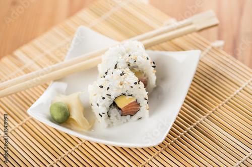 Tuinposter Sushi bar Zwei California Sushi mit Lachs und Mango an Holz Stäbchen
