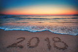 Happy New Year 2018 concept, lettering on the beach. Sea sunrise