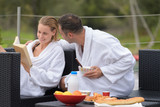 Couple relaxing while eating breakfast outdoors - 184210140