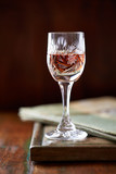 Glass of cherry liqueur on wooden table - 184212561