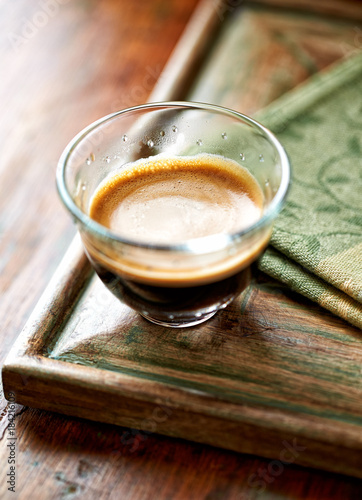 Glass of espresso on old wooden frame