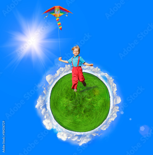 A child with a kite in his hands is on the Earth, on green grass. Around the sun, sky and clouds. Fantasy on the theme of family, childhood, future and happiness.
