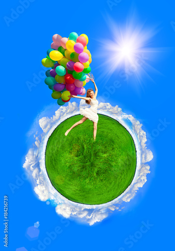 Happy birthday woman model against the sky with rainbow-colored air balloons in hands. sunny and positive energy of nature. Young beautiful girl on a ball of Earth with grass