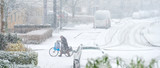 Man walking along his bike in the snow in winter