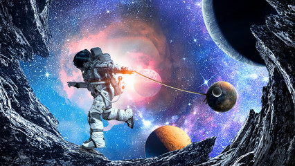 Fantasy image with spaceman catch planet. Mixed media © Sergey Nivens