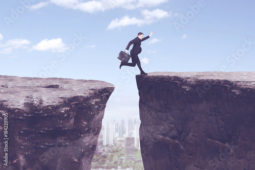 American manager jumping above gap cliff