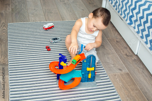 boy of five years playing toy cars and a road in a children's room