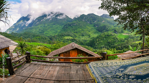 The panoramic view of forest and high mountains, which are covered with beautiful mist,  visible from the wooden terrace.of guesthouse . the roof made from grass 's leaves © kae2nata