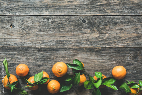 Tangerines with leaves on old wooden background. Food background. Top view with copy space for text