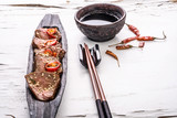 Slices of oriental spicy meat with sesame seads and pepper on long dark wooden plate with chopsticks and bowl of sauce on the white surface with cracked paint. Close up. - 184255349